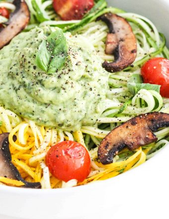 Zucchini noodles with creamy avocado pesto, sautéed mushrooms, tomatoes, and fresh basil
