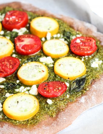 Homemade pizza topped with hemp seed pesto and summer squash, tomatoes, and feta