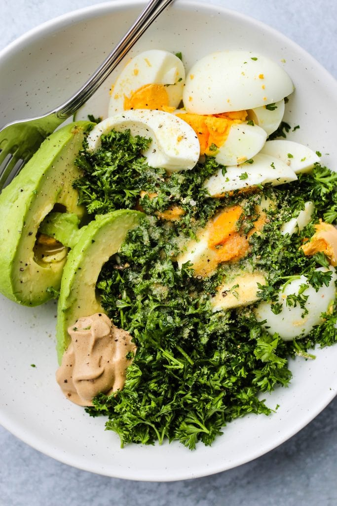 white bowl with avocado slices, hard boiled egg, parsley, mayo
