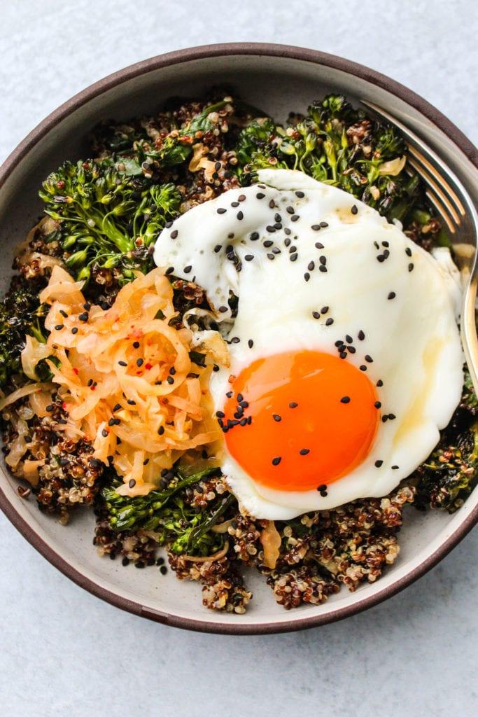 quinoa, kimchi, broccolini, and egg in bowl