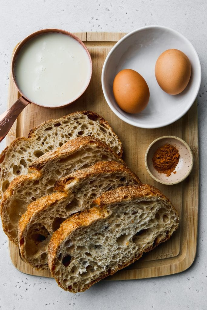overhead photo of wood cutting board with slices of bread, eggs, milk, and cinnamon on top