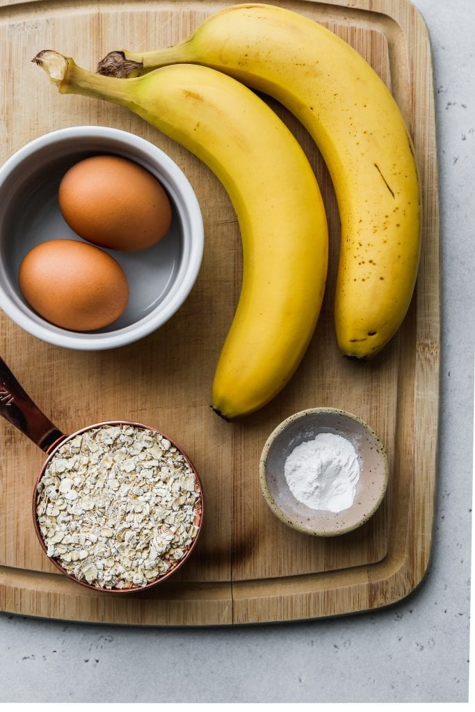 overhead photo of wood cutting board with bananas, oats, eggs, and baking powder on top
