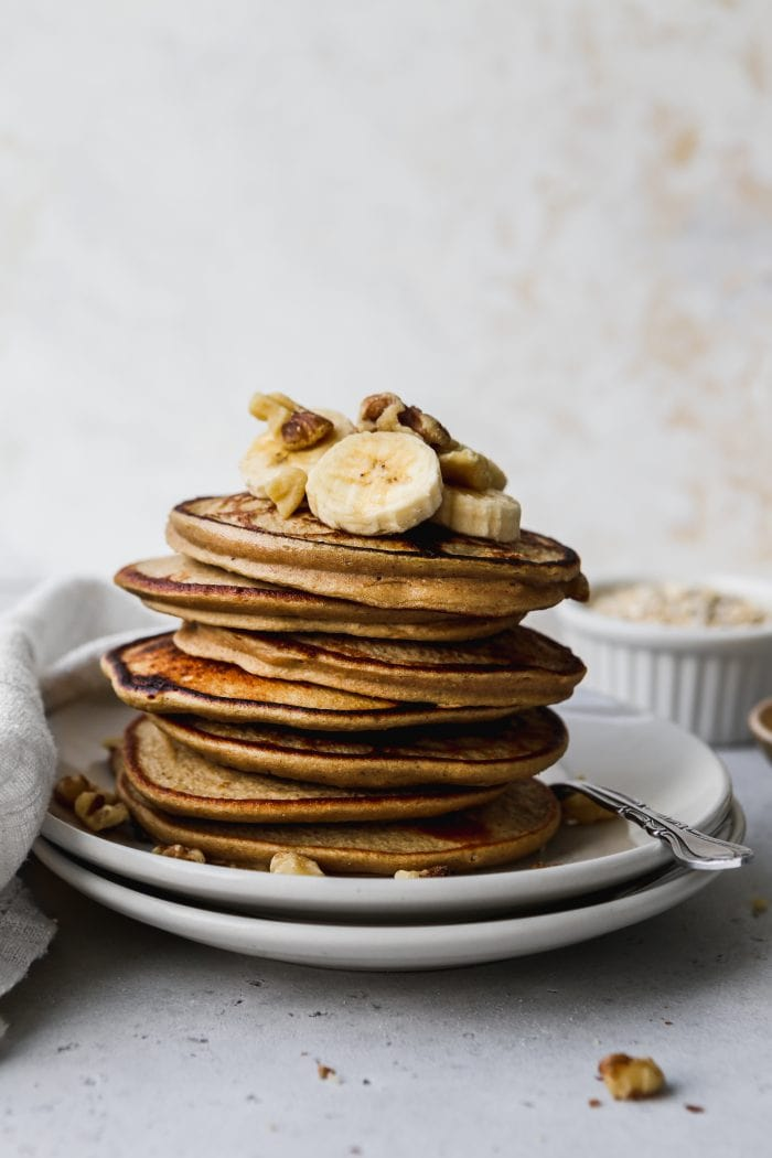 straight on closeup photo of a stack of banana oat pancakes on white plates