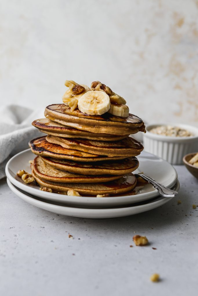 straight on photo of a stack of banana oatmeal pancakes on white plates