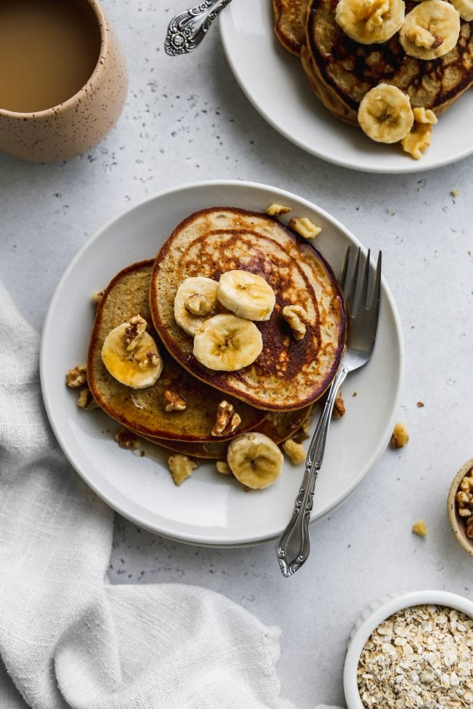 overhead photo of two white plates with stacks of banana oatmeal pancakes on top