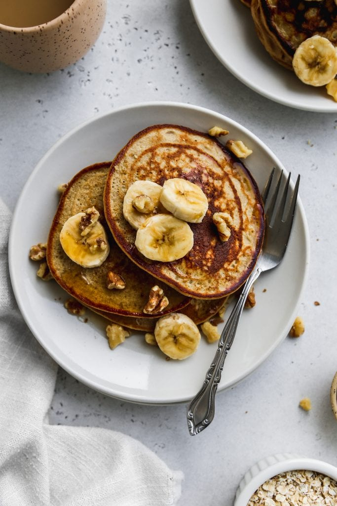 closeup overhead photo of two white plates with stacks of banana oatmeal pancakes on top