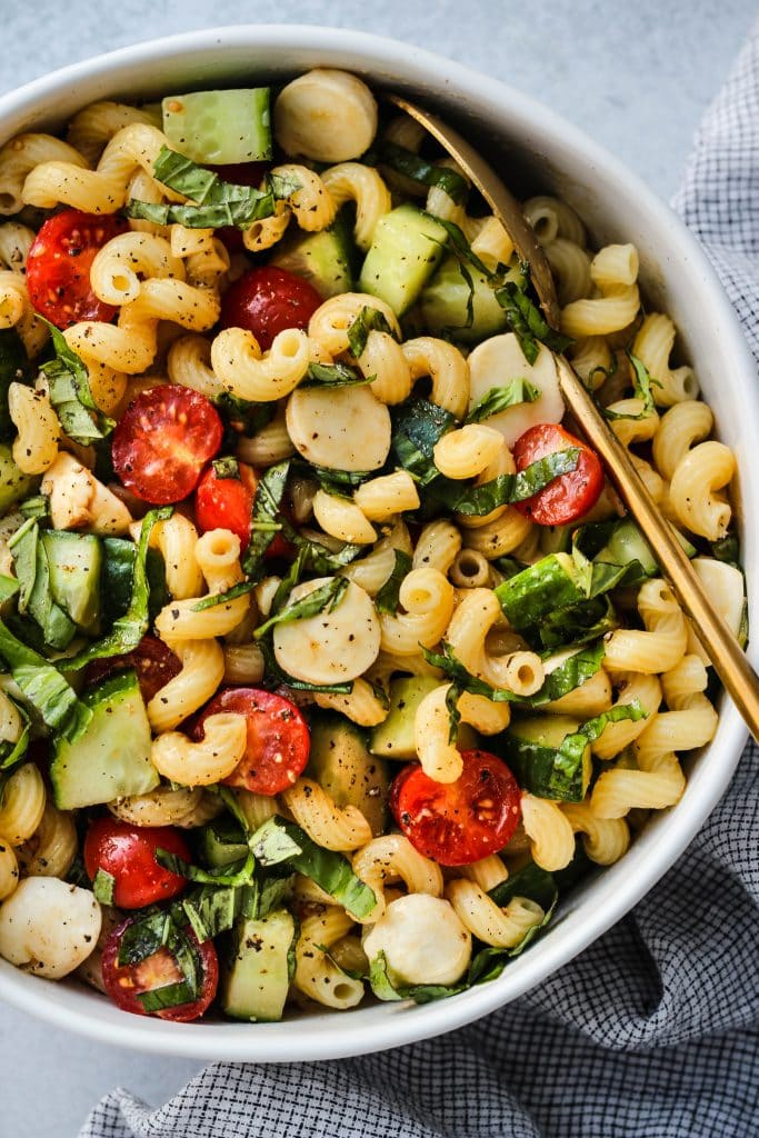 closeup shot of white bowl with cavatappi pasta, chopped cherry tomatoes, cucumbers, bocconcini, basil, and gold serving spoon