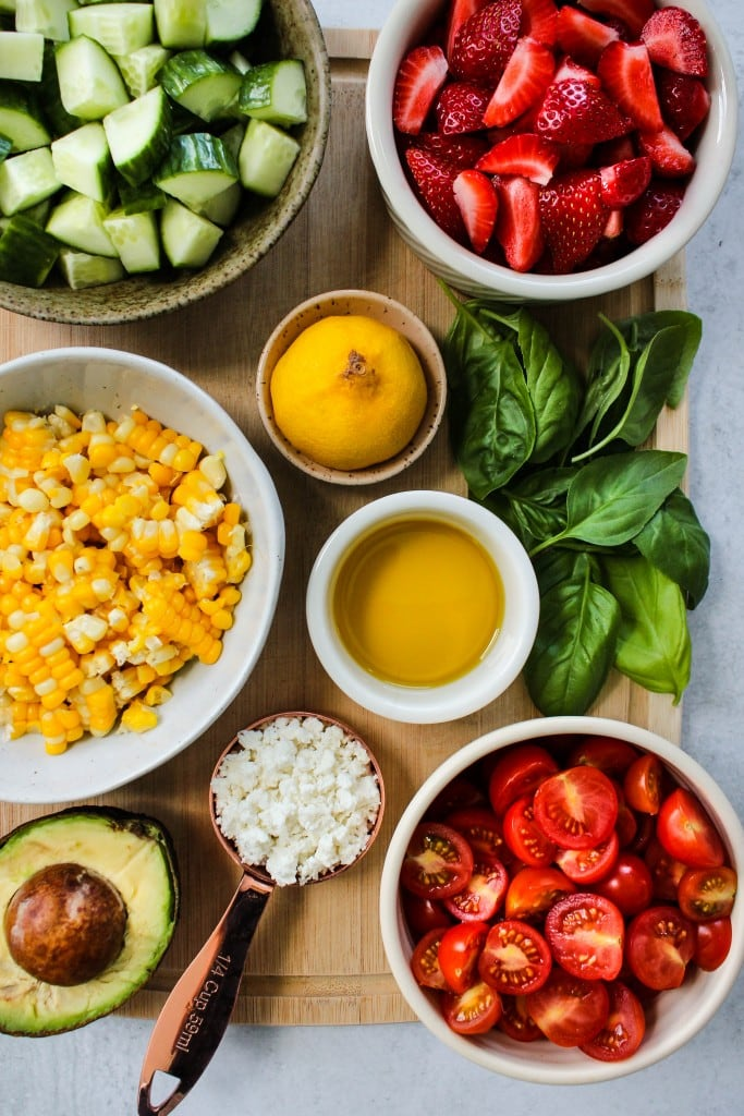 wood cutting board with bowls of chopped cucumbers, strawberries, corn, tomatoes, feta, avocado, basil, lemon, and olive oil