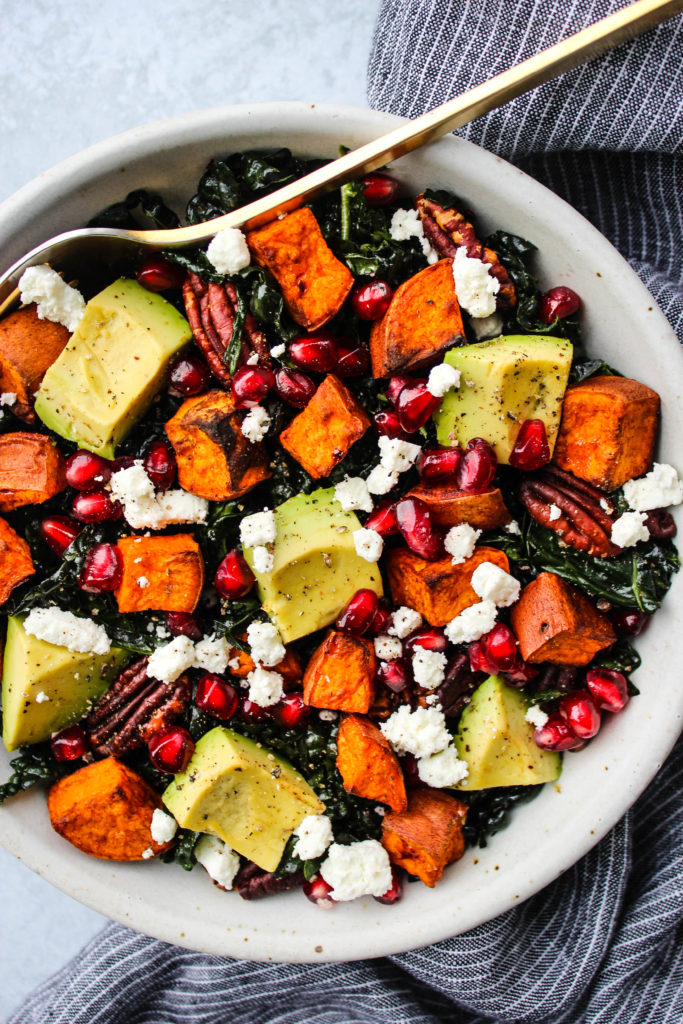 massaged kale salad with sweet potatoes, pomegranate, goat cheese, pecans, and avocado in white bowl