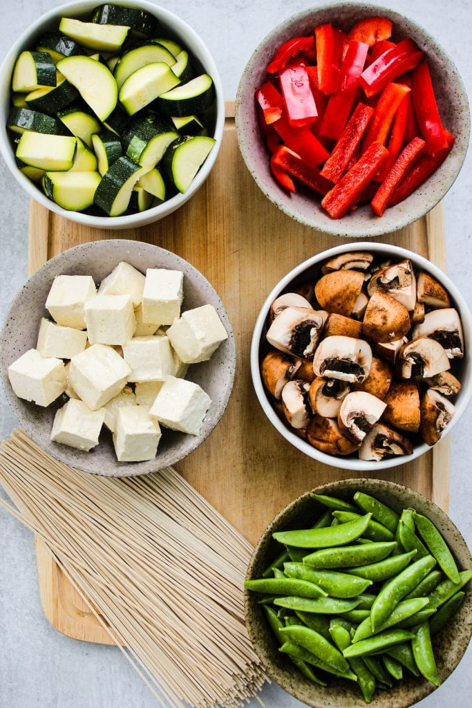 wood cutting board with bowls of vegetables and soba noodles