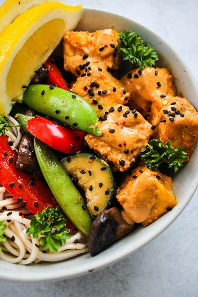 close up shot of light blue bowl with soba noodles, tofu, vegetables, and peanut sauce
