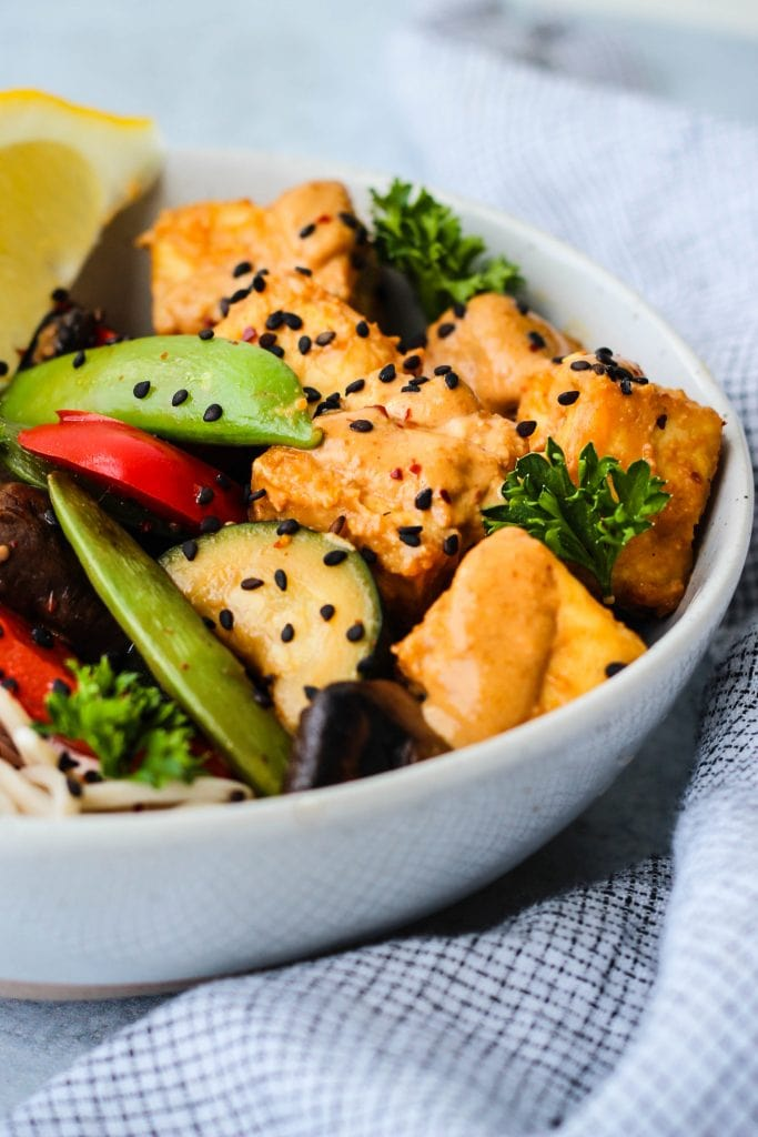 side angle shot of light blue bowl with soba noodles, tofu, vegetables, and peanut sauce