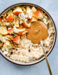grated apple bircher muesli topped with chopped apples, peanut butter, nuts, seeds