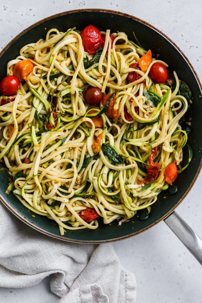 overhead photo of black skillet with cooked pasta with zucchini noodles, spinach and tomatoes