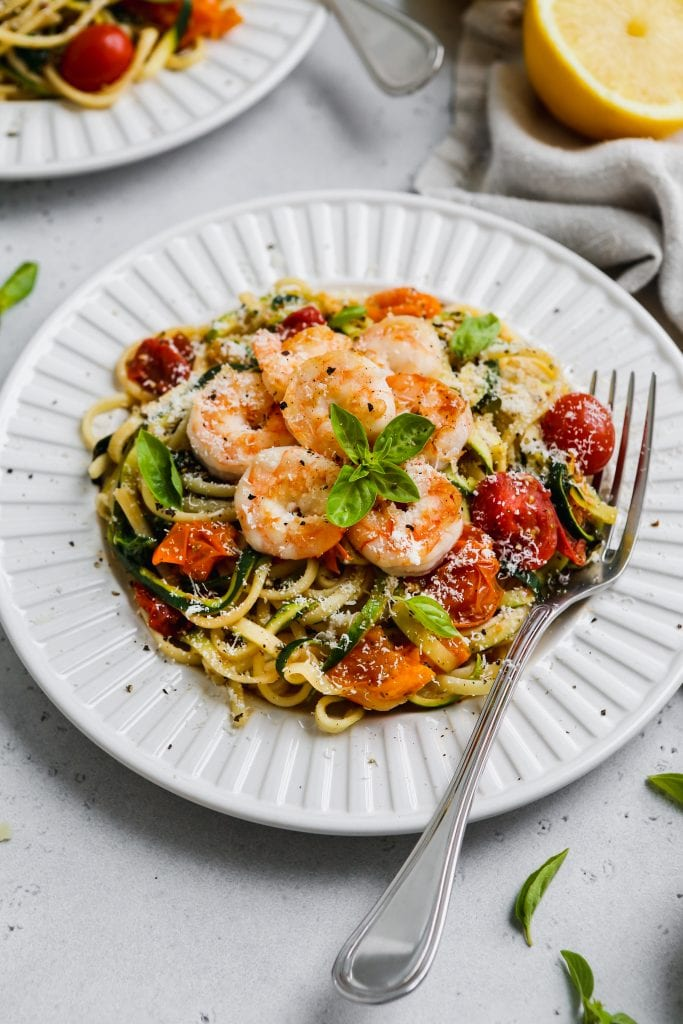 45 degree angle photo of white plate topped with spaghetti pasta, zoodles, tomatoes, spinach, and garlic prawns
