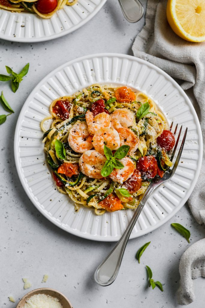 overhead photo of white plate topped with spaghetti pasta, zoodles, tomatoes, spinach, and garlic prawns