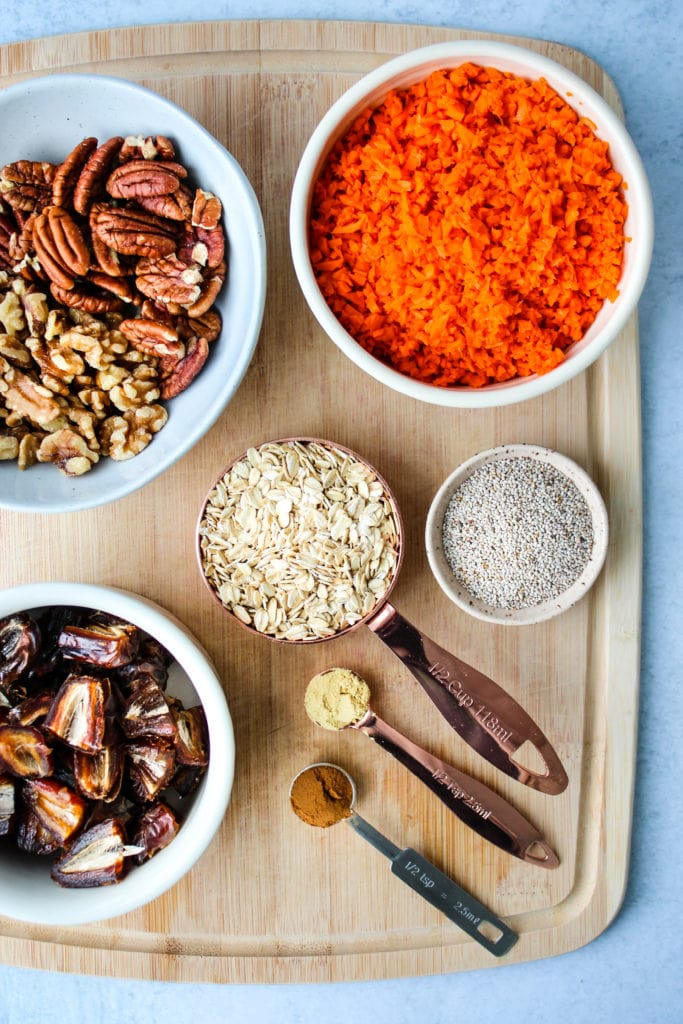 ingredients for energy bites on cutting board, including nuts, dates, carrots, oats, chia seeds, and spices