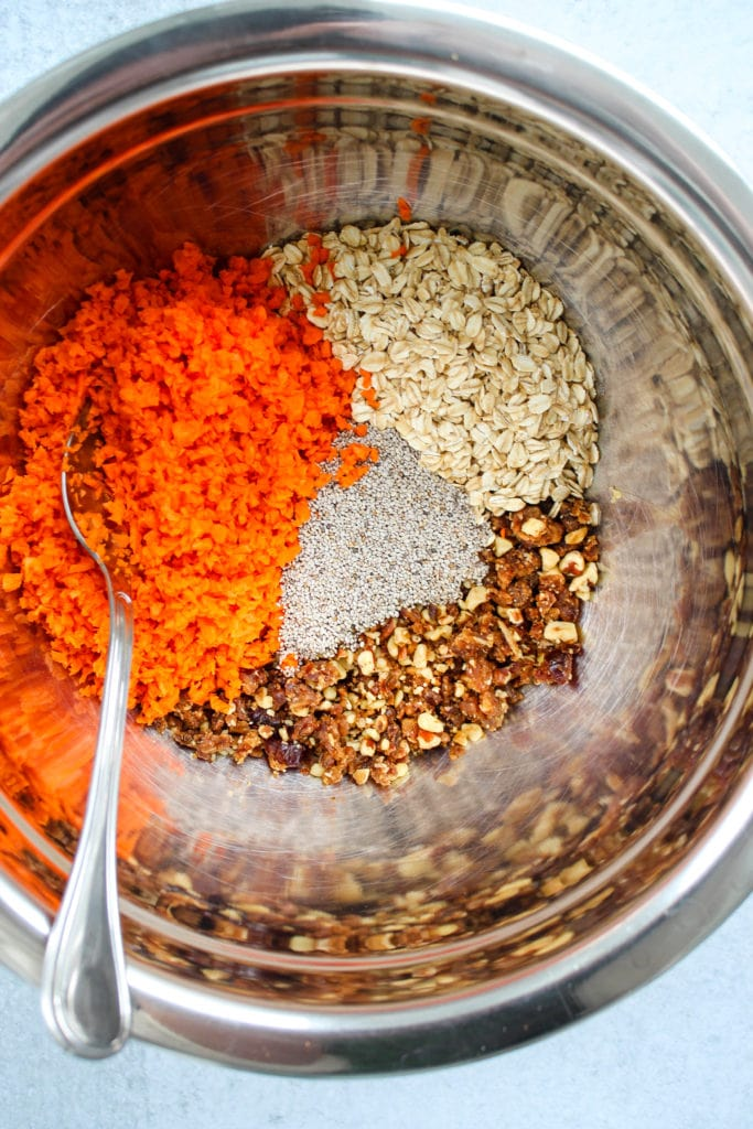 shredded carrots, oats, chia seeds, nuts, and dates in a mixing bowl