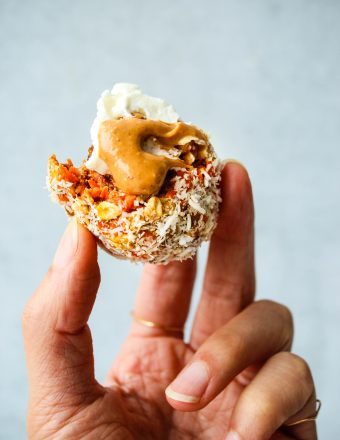 healthy no bake carrot cake energy bite with peanut butter and greek yogurt held in hand