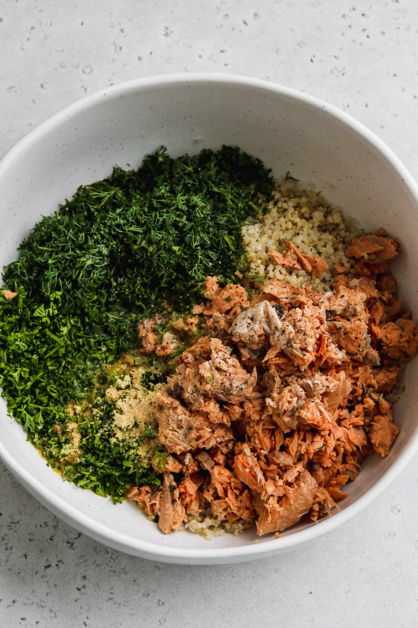Overhead photo of a large white mixing bowl filled with chopped herbs, quinoa, and canned salmon.