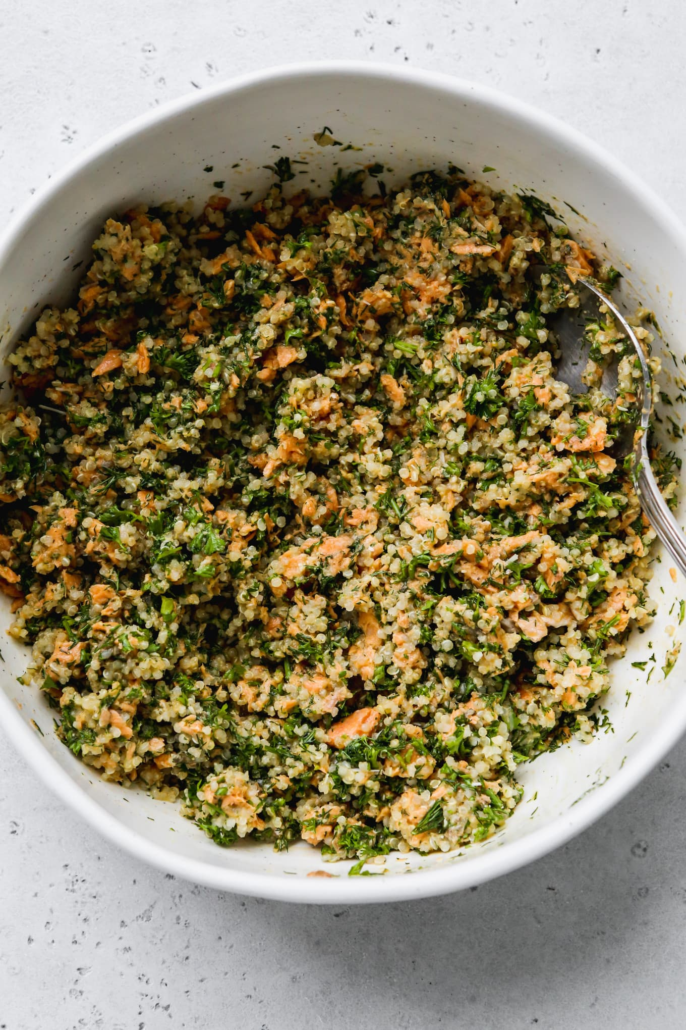 Overhead photo of a large white mixing bowl filled with chopped herbs, quinoa, and canned salmon mixed together.