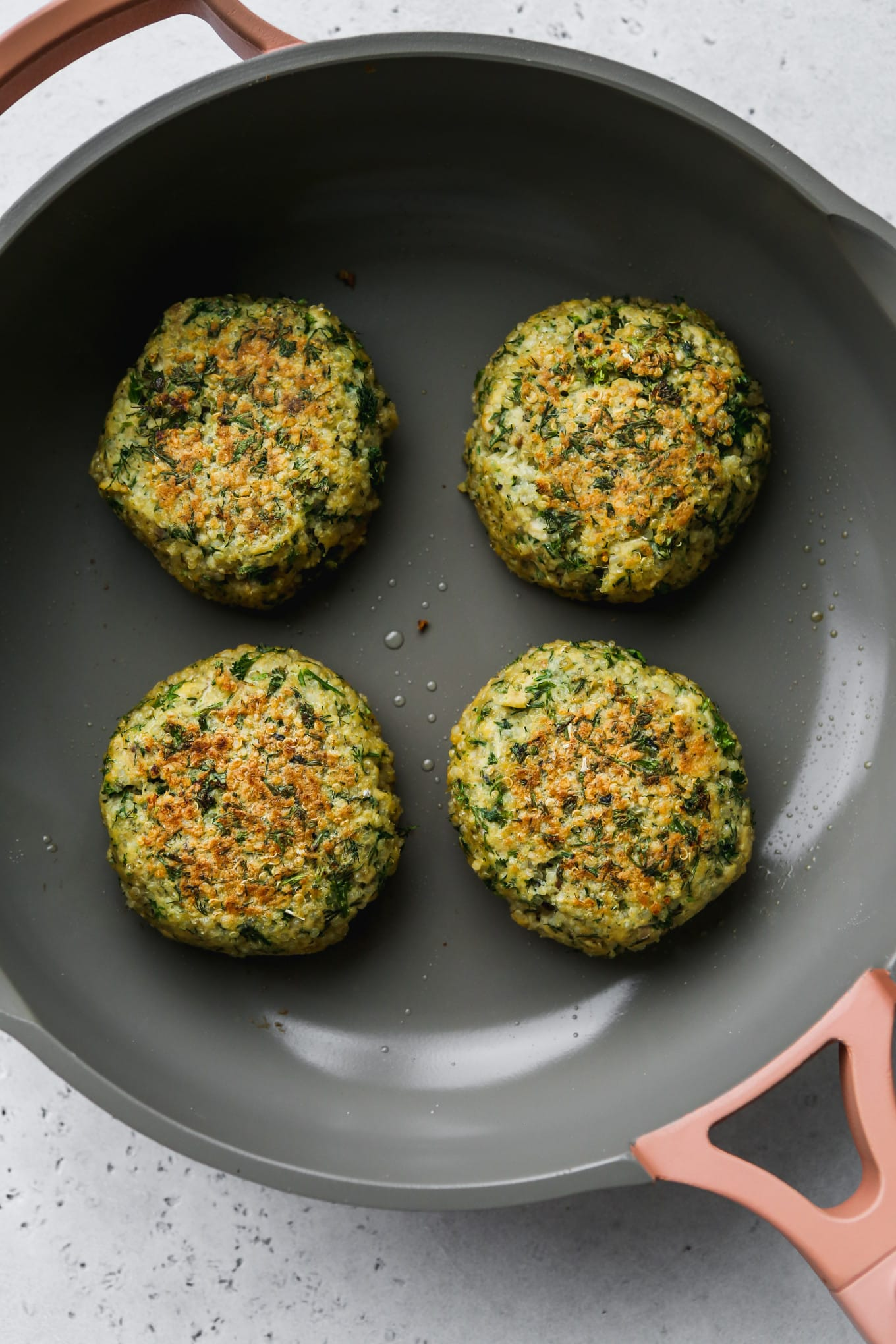 Overhead photo of 4 cooked salmon quinoa burger patties on a pan.