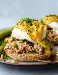 Whole wheat english muffin topped with canned salmon, a poached egg, hollandaise, and fresh parsley and dill on a plate.