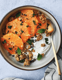 Bowl of Greek yogurt with sliced sumo citrus, fresh mint, cacao nibs, and granola