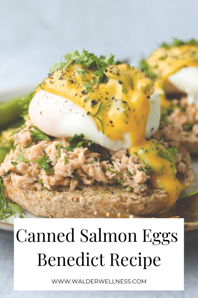 close up of english muffin topped with canned salmon, poached egg, hollandaise, and herbs
