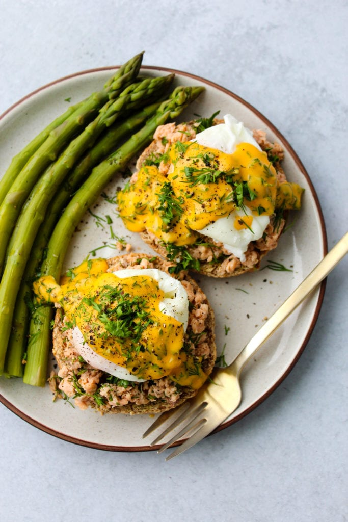 White plate with 2 english muffins topped with canned salmon, poached eggs, hollandaise, herbs, and a side of asparagus