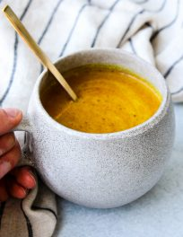 grey mug with golden mylk turmeric latte and gold spoon