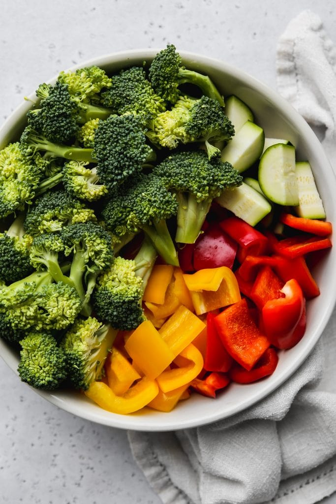 overhead photo of a large white bowl filled with chopped broccoli, bell peppers, and zucchini