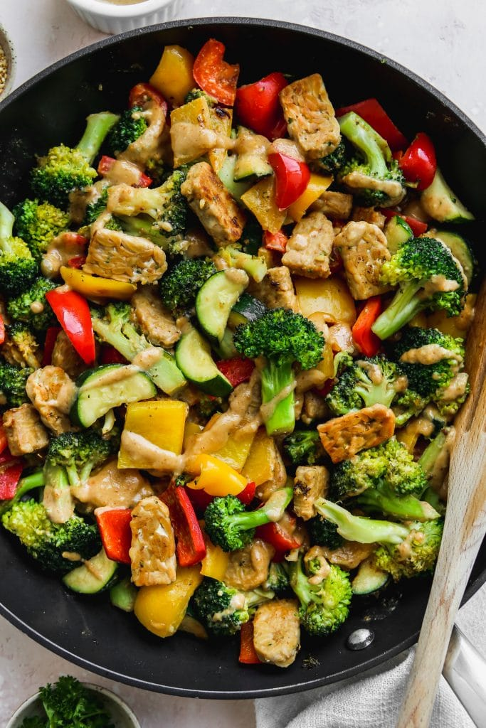 closeup photo of a black skillet with a tempeh, vegetable, and miso-peanut stir fry inside