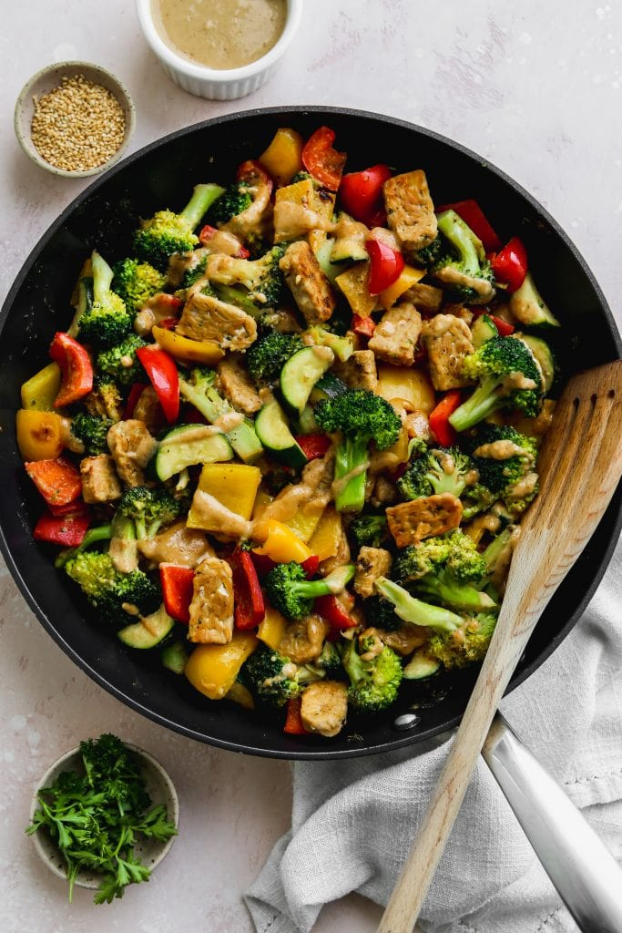overhead photo of a black skillet with a tempeh, vegetable, and miso-peanut stir fry inside