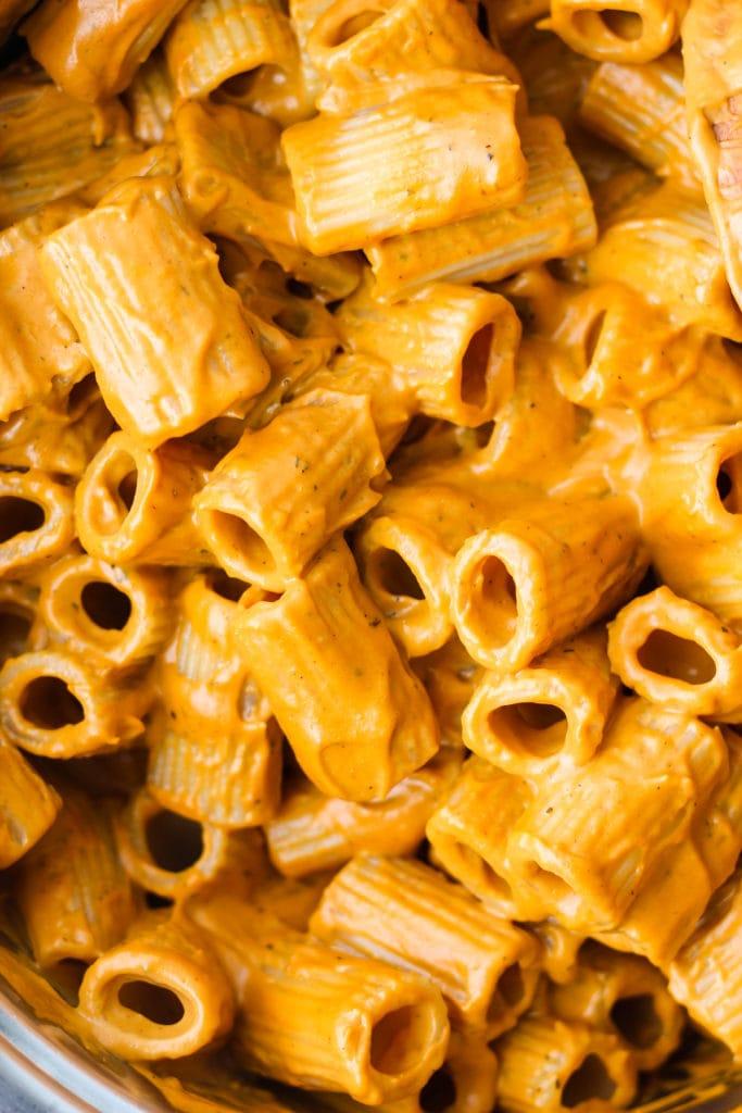 closeup of rigatoni pasta covered in roasted red pepper cashew cream sauce