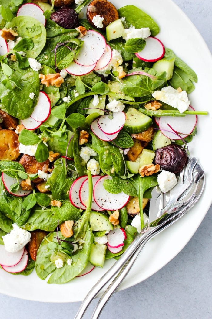Spinach salad with goat cheese, roasted potatoes, shaved radishes, and cucumbers in a while bowl with silver utensils