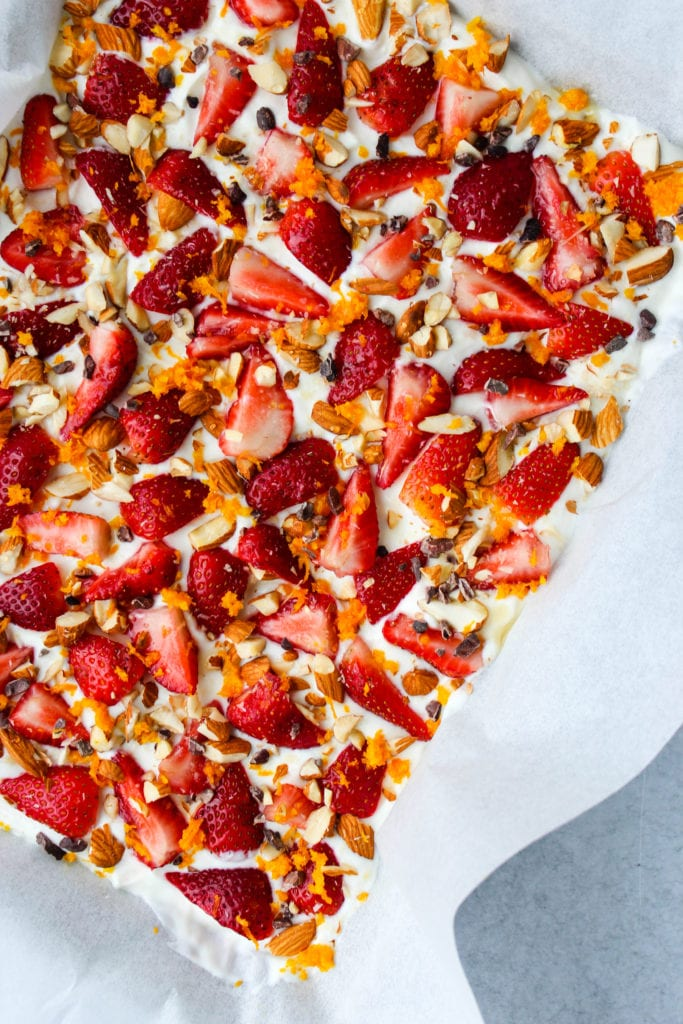 Baking sheet with parchment paper and frozen greek yogurt bark topped with chopped strawberries, orange zest, almonds, and cacao nibs
