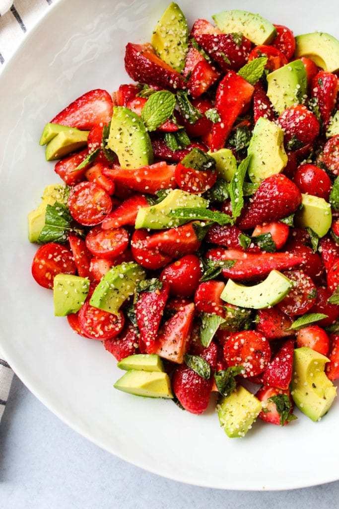 strawberry tomato avocado salad with mint, basil, balsamic, and hemp seeds in a white bowl