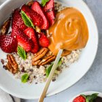 white bowl with steel cut oatmeal topped with sliced strawberries, mint leaves, pecans, and peanut butter