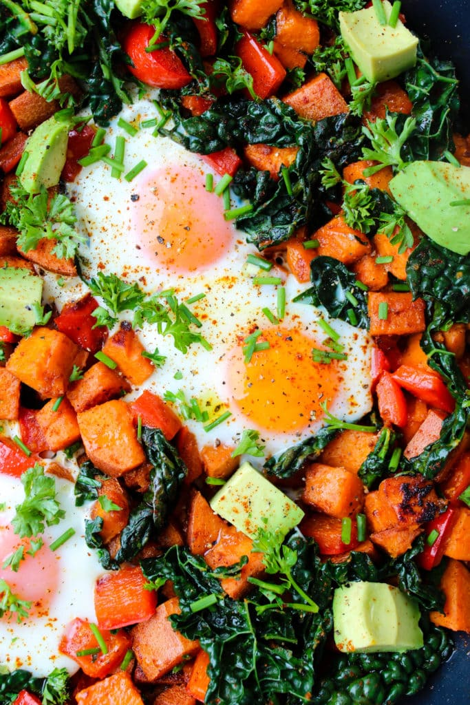 Closeup of breakfast skillet with chopped sweet potatoes, red bell pepper, kale, avocado, and runny eggs