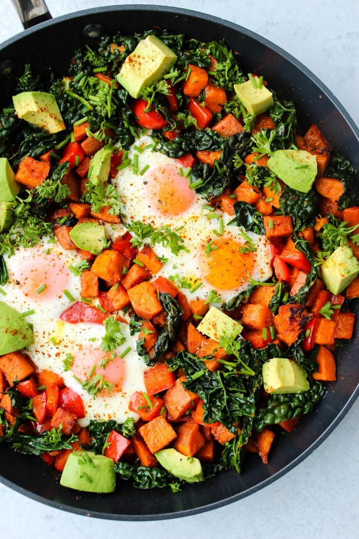Sweet potato hash with red bell peppers, kale, avocado, and eggs in a skillet