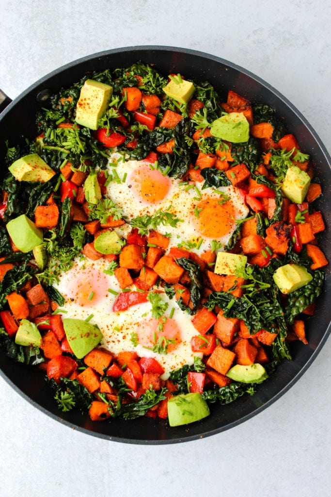Overhead shot of black skillet with sweet potato, red pepper, and kale hash, eggs, and chopped avocado