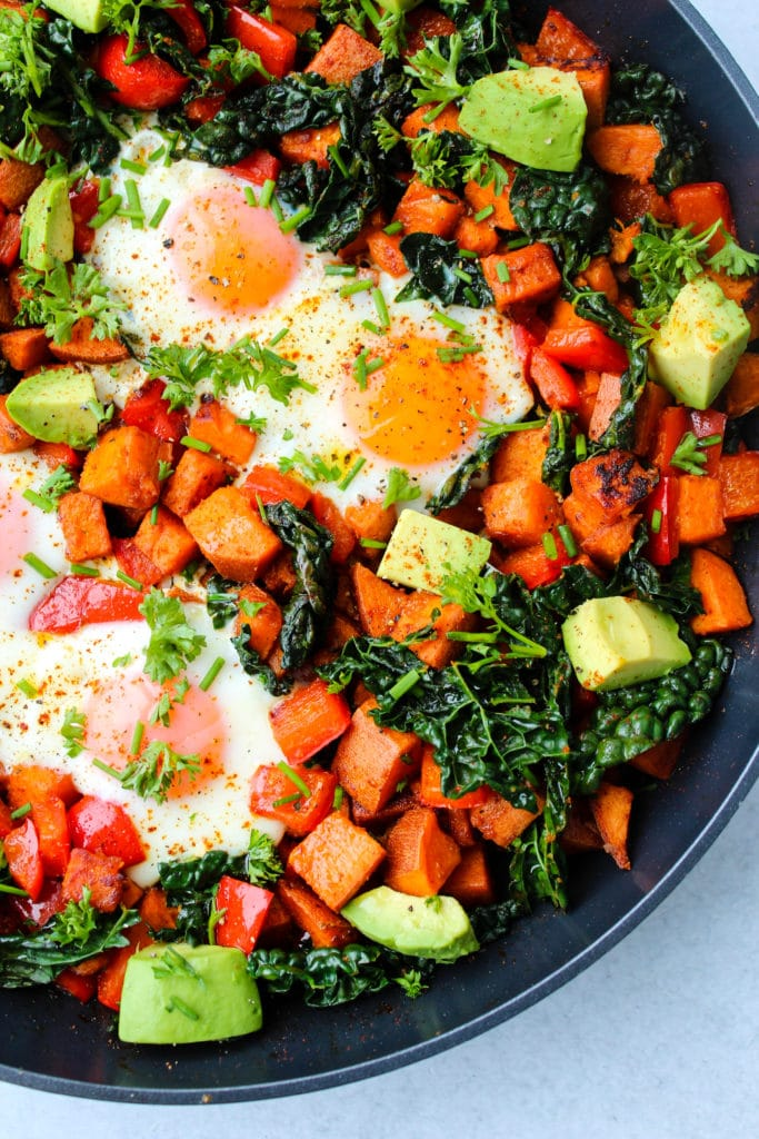 Black skillet with sweet potato hash topped with kale, red bell peppers, avocado, four eggs, and fresh herbs