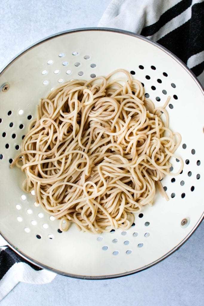 white colander with cooked soba noodles