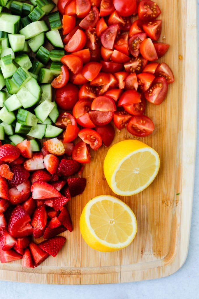 Overhead photo of chopped cucumber, tomatoes, strawberries, and lemon on a wooden cutting board.