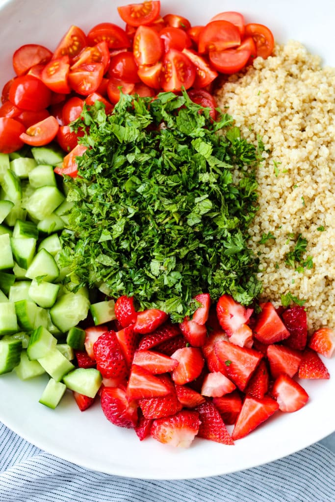 Overhead photo of chopped tomatoes, cucumbers, strawberries, parsley, mint, and quinoa in a large white bowl.