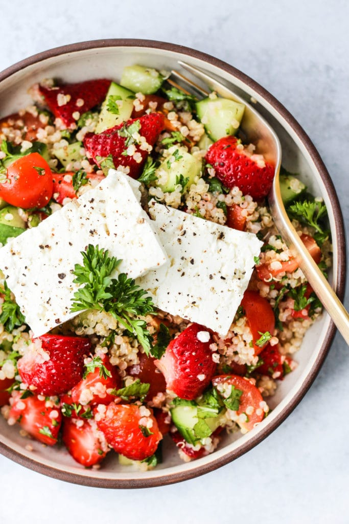 Overhead photo of small bowl with strawberry quinoa salad inside and 2 pieces of feta cheese on top.