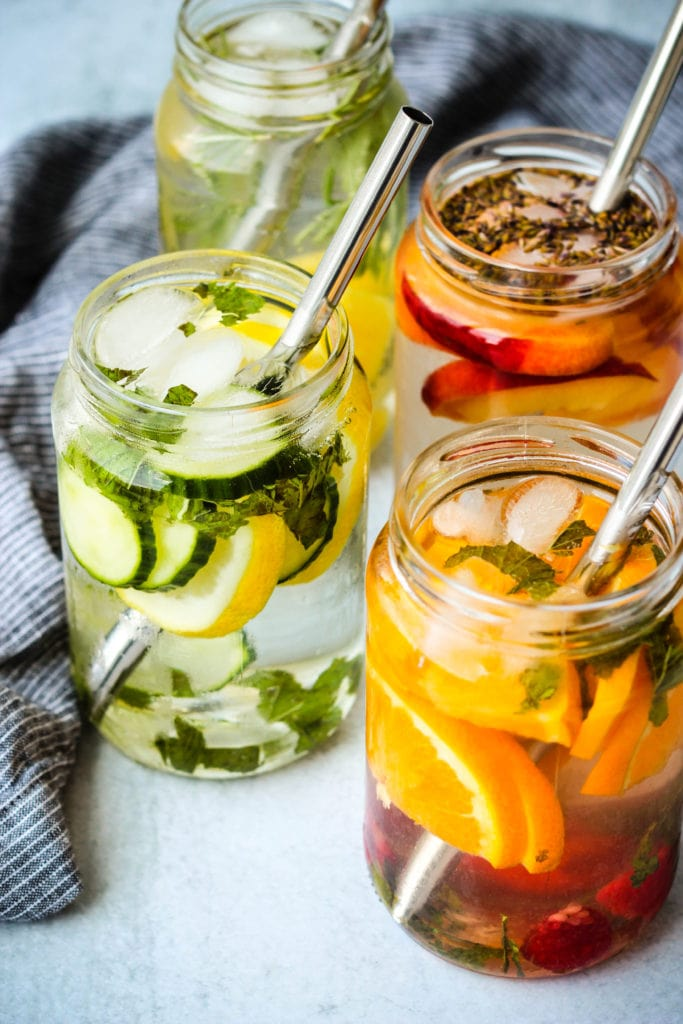 4 glass jars with fruit infused water