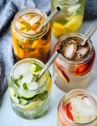 5 glass jars with fruit-infused water and metal straws