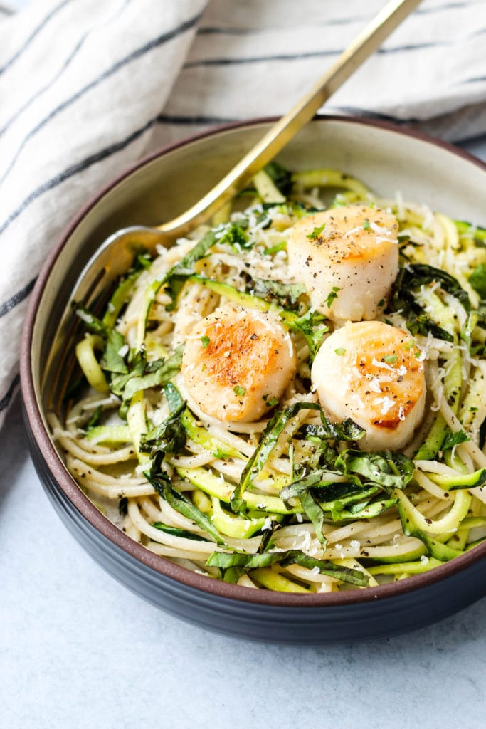 spaghetti and zucchini noodles topped with pan seared scallops in a brown bowl